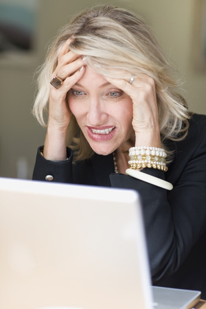 hardships: Frustrated businesswoman using laptop