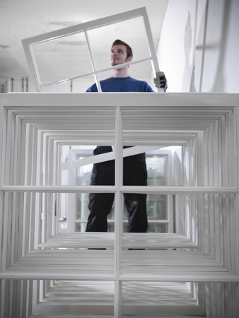 stockmarket: Worker holding window frames in joinery