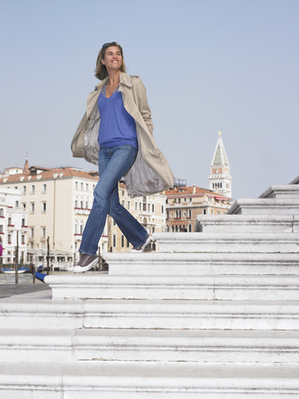 southern european descent: Woman on stairs by the marina