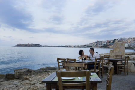 Couple sitting at waterfront cafe LANG_EVOIMAGES