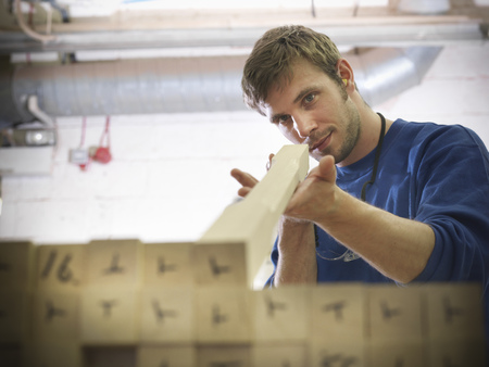 alignments: Worker examining wood in joinery