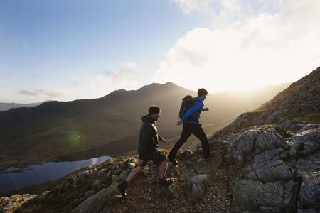mountainous: Men hiking on rocky mountainside