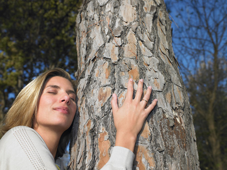defended: Woman hugging a tree LANG_EVOIMAGES