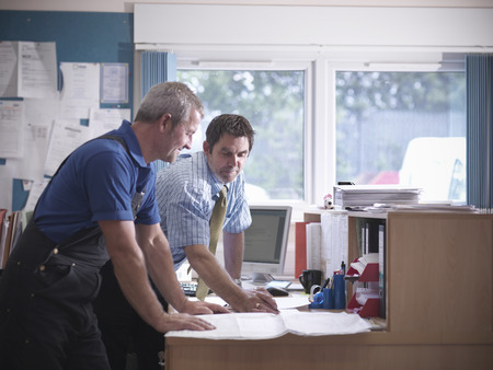 conferring: Businessman and worker in office