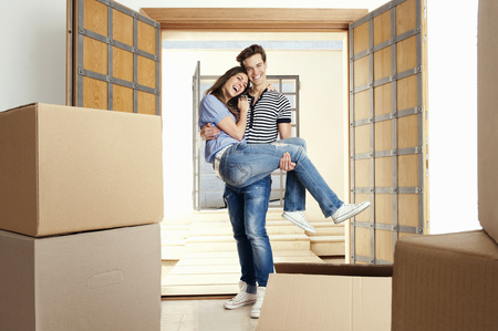 accomplishes: Man carrying girlfriend over threshold