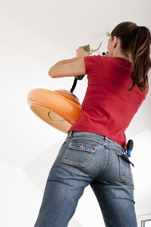 accomplishes: Woman fixing broken lamp LANG_EVOIMAGES