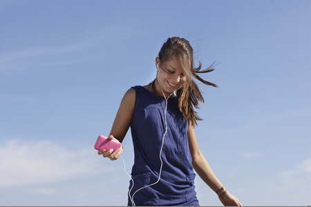 Woman with musicplayer jumping