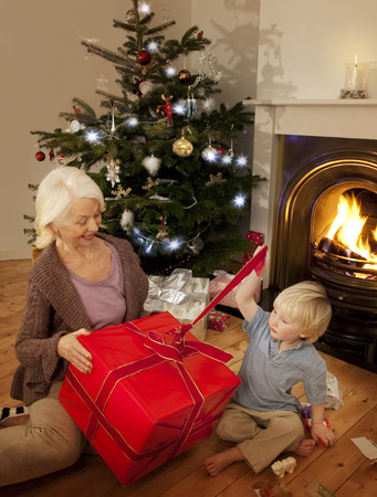 generation gap: Grandson opens a present with his Granny LANG_EVOIMAGES