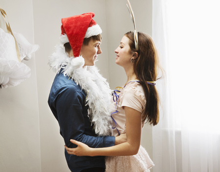 rejoices: Couple embracing wearing christmashats