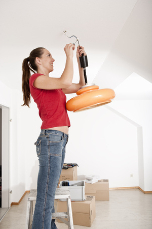 Woman fixing lamp in new home