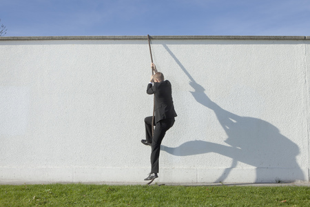struggled: Businessman climbing over wall with rope