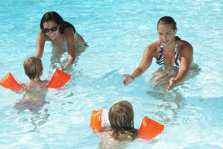 Women teaching to kids how to swim LANG_EVOIMAGES