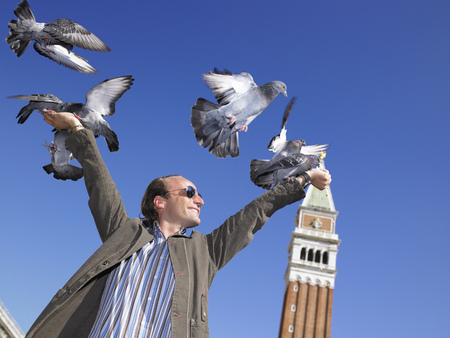 Man with pigeons on his hands LANG_EVOIMAGES