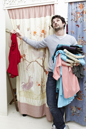 resolving: Man holding clothes by a changing room LANG_EVOIMAGES
