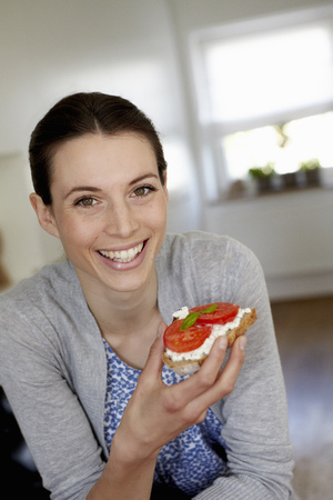 snacking: Smiling woman eating tomato sandwich LANG_EVOIMAGES