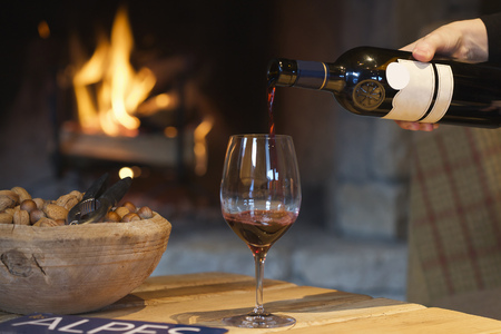 Person pouring wine by fireplace