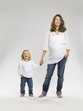 equivalents: Pregnant woman holding daughter's hand
