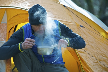 survives: Man cooking food by camping tent
