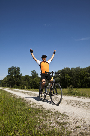 prevailing: Biker cheering on dirt road LANG_EVOIMAGES