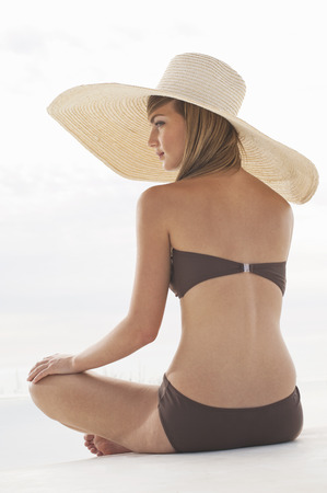 shadowed: Woman in a swimsuit and large hat LANG_EVOIMAGES