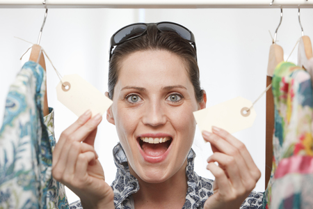 woman smiling holding price tags LANG_EVOIMAGES