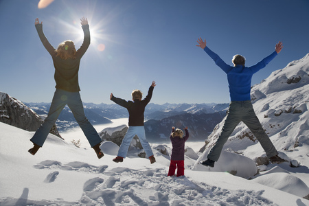 remoteness: Happy family jumps in winter mountains