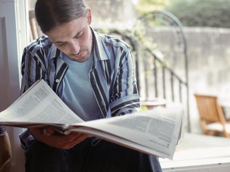 held down: Man reading newspaper LANG_EVOIMAGES