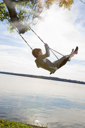 joyous: Boy swinging from tree by lake