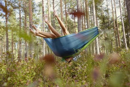 Women relaxing in hammock in forest