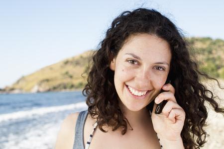 reconocimientos: Mujer que habla en el teléfono celular en la playa