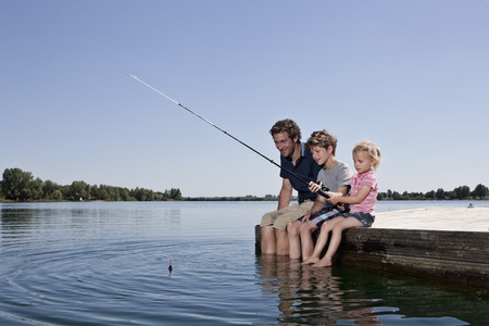 Father and children fishing on dock