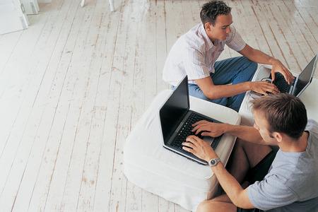 telecommuter: Men using laptops in living room LANG_EVOIMAGES