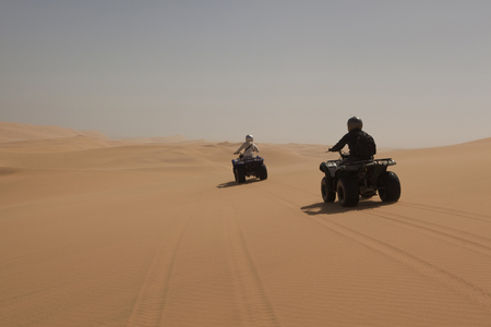 remoteness: People driving four wheelers on sand
