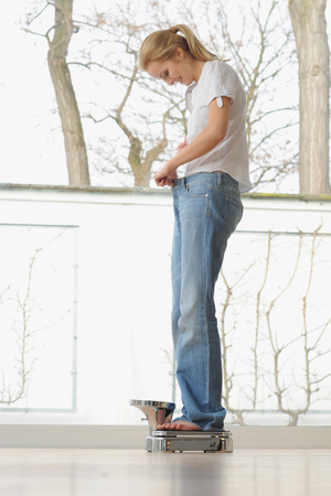fulfilled: Woman wearing large jeans on scale