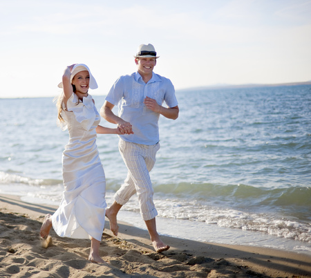 obligations: Newlywed couple running on beach