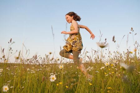 saltar: Girl running in field of flowers