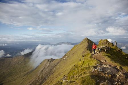 adventuring: Hiker walking on rocky mountaintop LANG_EVOIMAGES