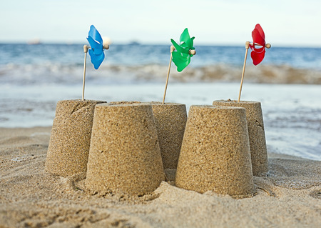 conforms: Sandcastles with pinwheels on beach LANG_EVOIMAGES