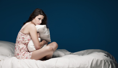 Teenage girl hugging pillow on bed LANG_EVOIMAGES