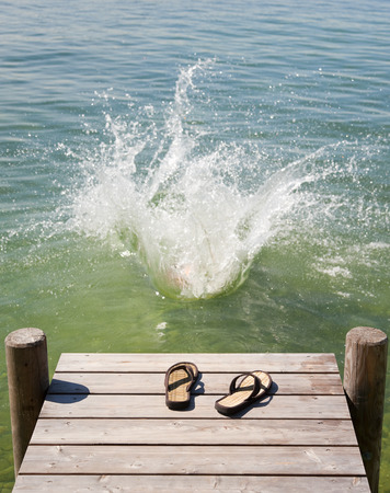 spattered: Flip flops on wooden deck by lake