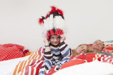 mischeif: Boy wearing war bonnet in parents' bed