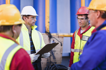 meets: Workers talking on oil rig