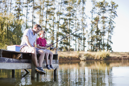 Father fishing with son in lake LANG_EVOIMAGES