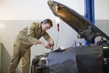 down lights: Mechanic working on car engine in garage