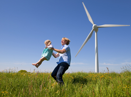 Man in daughter in field by wind turbine LANG_EVOIMAGES