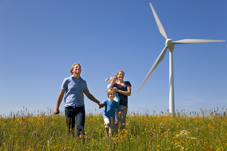 Family walking in field by wind turbine
