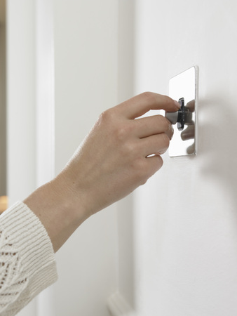 Woman turning on light switch