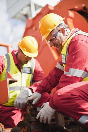 Worker turning wheel on oil rig LANG_EVOIMAGES
