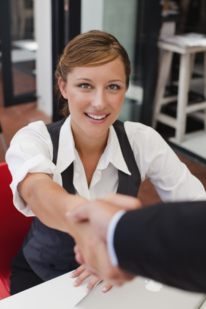 cerrando negocio: Empresarios agitando las manos en la mesa
