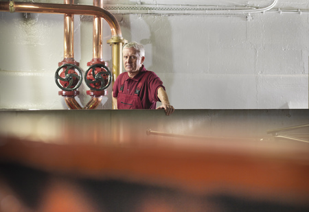 assessed: Worker checking whisky in distillery